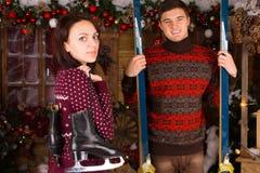 Paare mit Rochen und Skis vor Blockhaus Lizenzfreies Stockfoto