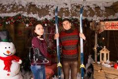 Paare mit Rochen und Skis vor Blockhaus Lizenzfreie Stockfotos