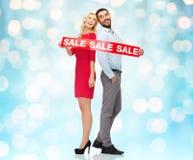 Paare mit rotem Verkauf unterzeichnen Stellung, um sich zurückzuziehen Lizenzfreie Stockfotos