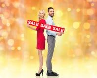 Paare mit rotem Verkauf unterzeichnen Stellung, um sich zurückzuziehen Lizenzfreie Stockbilder
