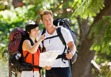 Paare mit Rucksäcken und Karte Lizenzfreie Stockbilder