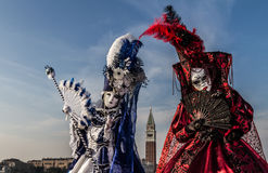Paare mit schönem Kostüm und venetianische Maske während Venedig-Karnevals mit Glockenturm im Hintergrund Lizenzfreie Stockfotos