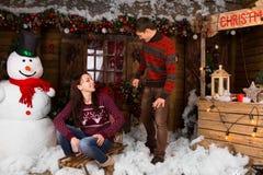 Paare mit Schlitten draußen im Winter am Blockhaus Lizenzfreie Stockbilder