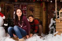 Paare mit Schlitten draußen im Winter an der Kabine Stockfotos