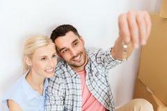 Paare mit Schlüssel und Kästen, die auf neues Haus sich bewegen Stockfotografie