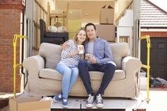Paare mit Sofa On Tail Lift Of-Abbau-LKW-beweglichem Haus Lizenzfreie Stockfotografie
