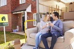 Paare mit Sofa On Tail Lift Of-Abbau-LKW-beweglichem Haus Stockfoto