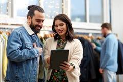 Paare mit Tabletten-PC am WeinleseBekleidungsgeschäft Stockfoto