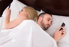 Paare mit Telefonen im Bett Stockfotos