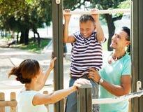Paare mit Training des jugendlichen Sohns ziehen an Stange hoch Lizenzfreie Stockfotos