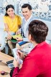 Paare mit Verkäufer im Möbelgeschäft Lizenzfreie Stockbilder