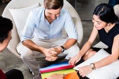 Paare mit Verkäufer im Möbelgeschäft Lizenzfreie Stockfotos