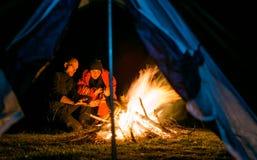 Paare nähern sich dem Lagerfeueraufwärmen Stockbild
