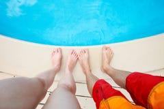Paare nähern sich Swimmingpool Stockfoto