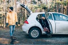 Paare nahe bei kleinem hybridem Auto im Wald lizenzfreie stockfotos