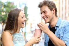 Paare oder Freunde, die ein Milchshaken teilen stockbilder