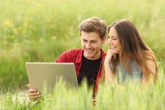 Paare oder Freunde, die einen Laptop teilen Lizenzfreie Stockbilder