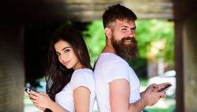 Paare plaudernde Smartphones Mädchen und bärtiger Mann stehen zurück zur hinteren Veranda oder Untertage Paare ignorieren wirklic stockbild