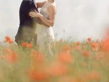 Paare in Poppy Field Lizenzfreies Stockfoto