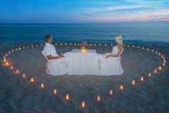 Paare am romantischen Abendessen des Strandes mit Kerzenherzen Lizenzfreies Stockfoto