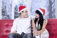 Paare in Sankt-Hut, der auf roter Couch sitzt Stockfoto
