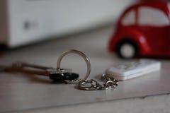 Paare Schlüssel mit einem Schlüsselring auf einer Tabelle auf einem Hintergrund eines roten Autos lizenzfreie stockbilder