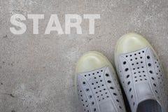 Paare Schuhe, die auf einer Straße mit ANFANGSkonzept stehen Lizenzfreie Stockbilder