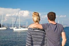 Paare am Segelnfeiertag mit Segelboot im Hintergrund Stockfotografie