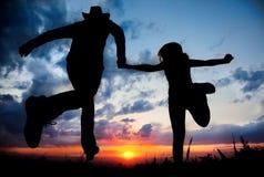 Paare silhouettieren Betrieb zum Sonnenuntergang lizenzfreie stockfotos