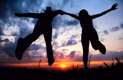Paare silhouettieren Betrieb zum Sonnenuntergang Stockfotografie