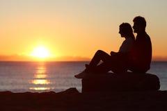 Paare silhouettieren sitzende aufpassende Sonne bei Sonnenuntergang Stockfotografie