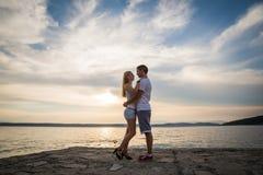 Paare silhouettieren am Strand Stockfoto