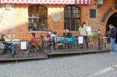 Paare sind an einer szenischen Caféterrasse im Freien in der alten Stadt von Vilnius, Litauen entspannend Stockbild
