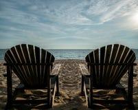 Paare sitzen auf sonnigem Strand vor Lizenzfreies Stockfoto