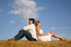 Paare sitzen auf Wiese Stockfoto