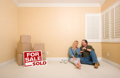 Paare sitzen nahe Kästen und Verkaufsgrundbesitz-Zeichen Lizenzfreies Stockfoto