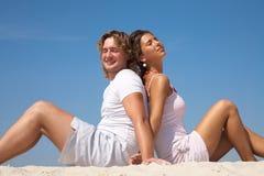 Paare sitzen am Strand lizenzfreie stockfotos