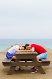 Paare sitzen zusammen am Tisch nahe dem Strand lizenzfreie stockfotografie