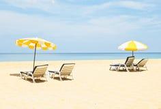 Paare Sonnenruhesessel und Strandschirme auf dem Strand Lizenzfreie Stockfotos