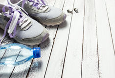 Paare Sportschuhe, Wasserflasche und Kopfhörer auf weißem Holz Lizenzfreie Stockfotos
