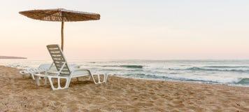 Paare Strand deckchairs auf Küste mit Regenschirm vor Meer, Sonnenuntergang, hintere Ansicht stockfotos