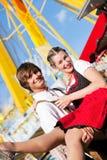 Paare in Tracht, das am großen Rad flirtet Stockbilder