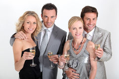 Paare in trinkendem Champagner des Partykleides stockfoto