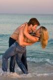 Paare umfassen in der Brandung Lizenzfreies Stockfoto
