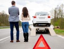 Paare und defektes Auto auf einer Landstraße Lizenzfreie Stockfotos