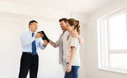 Paare und Grundstücksmakler mit Tabletten-PC am neuen Haus Stockfotografie