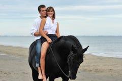 Paare und Pferd auf dem Strand Stockfoto