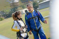Paare ungefähr zum Springen in Fallschirme Stockfotos