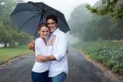Paare unter einem Regenschirm Stockbild