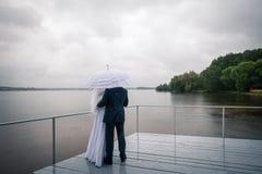 Paare unter einem Regenschirm im regnerischen Wetter Stockfotografie